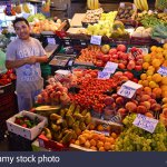 cheerful-shopkeeper-at-fruits-and-vegetables-stall-la-boqueria-market-f0ajf8